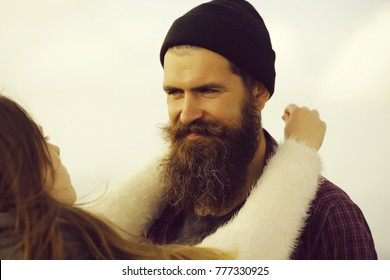 Pretty girl holds bearded man hipster with beard and moustache outdoors on natual environment on foggy sky