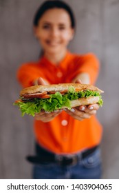 a pretty girl holds a delicious sandwich with vegetables and meat and salad. An ideal concept for advertising a cafe, restaurant, or fast food with sandwiches