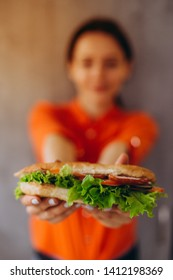 a pretty girl holds a delicious sandwich with vegetables and meat and salad. An ideal concept for advertising a cafe, restaurant, or fast food with sandwiches. close up photo of sandwich in cafe table