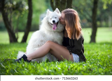 Pretty girl hugging and kissing her dog at the park outdoor, samoyed