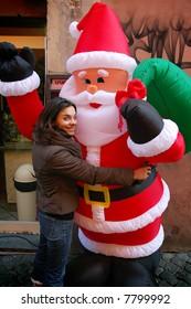 Pretty girl hugging Santa at Christmas