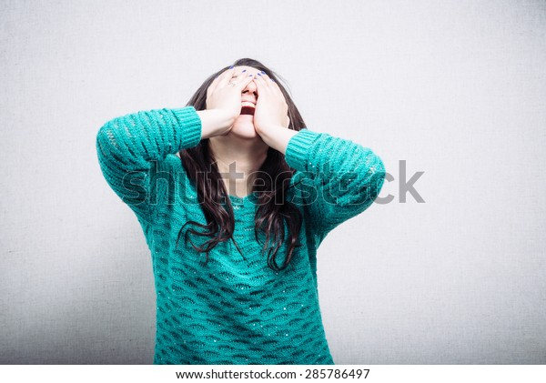 Pretty girl in hysterics covers her face