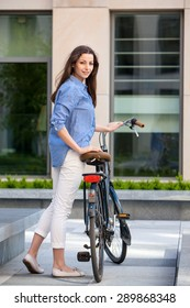 Pretty girl iin blue shirt with a bicycle at street