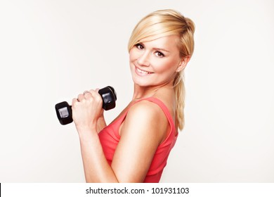 Pretty girl keeping her beautiful shape exercising with hand weights and a smile