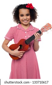 Pretty girl kid loves music. Holding toy guitar in hand.