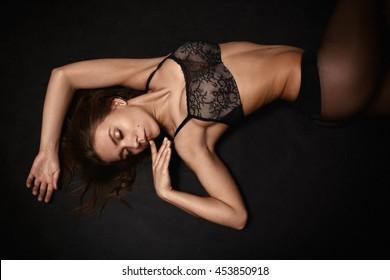 pretty girl in lingerie lying on black background