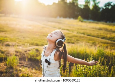 Pretty girl listening music with headphones and having rest, lucky child listening music and resting
