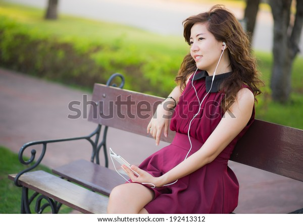The pretty girl listening music with mobile phone