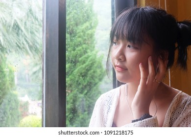 Pretty girl is listening nice music. she look through the windows on a rainy day.