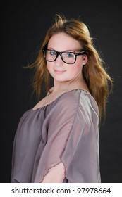 Pretty girl with long brown hair wearing vintage glasses isolated on dark background. Studio portrait.