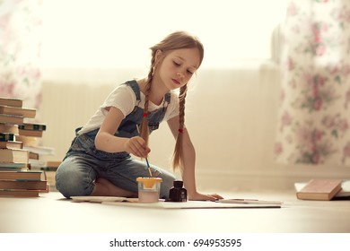 Pretty girl with long hair in combinazione draws on the floor