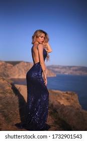 Pretty girl with long hair in elegant dress posing on beach