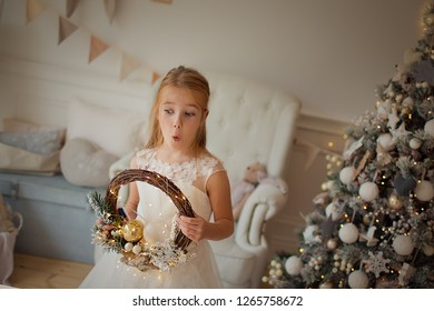 A pretty girl with long hair is holding a Christmas wreath. New year and Christmas.