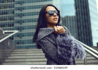 Pretty girl with long hair poses in the city streets.