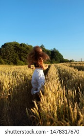 The pretty girl with long hair in stylish white pants and black top running in rye .Stylish .Long haired,curly girl.Girl in rye.Summer photos of a beautiful girl in the field. Dynamic .Sunset light