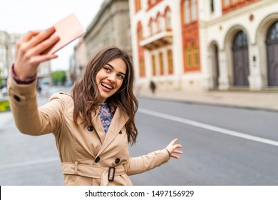 Pretty girl with long hair takes a selfie in the city streets. Beautiful young photographer takes pictures for her travel blog. Young girl take selfie from hands with phone on summer city street.
