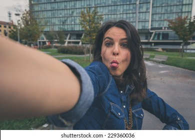 Pretty girl with long hair takes a selfie in the city streets