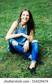Pretty girl with long hair and torn jeans smiling with closed eyes sitting on grass in park outdoor