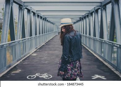 Pretty girl with long hair walking away on a bridge