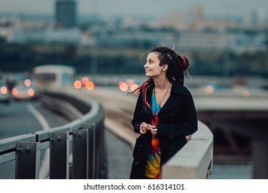 Pretty girl with long hair walking away on a bridge. Girl with dreadlocks walking in the city on a bridge. Stands next to the fence close