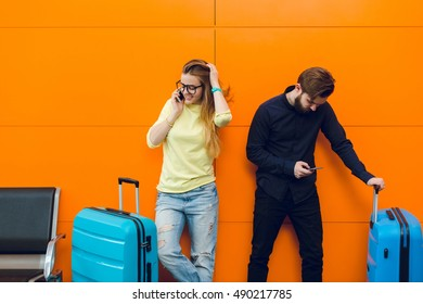 Pretty girl with long hair in yellow sweater  is speaking on phone on orange background. Young guy with beard in black shirt is standing near her. The are between suitcases.