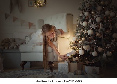 A pretty girl with long red hair sits in the dark near the Christmas tree, a magical light, waiting for the new year and Christmas, considering gifts. New year and Christmas.