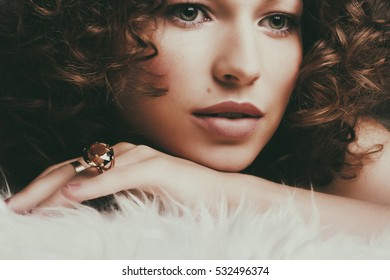 Pretty girl with long and shiny wavy hair . Beautiful model with curly hairstyle. Jewelry and Beauty. Fashion art photo