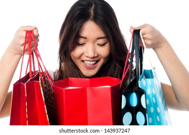 Pretty girl looking inside shopping bags