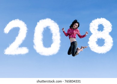 Pretty girl looks happy while dancing with clouds shaped numbers 2018 in the blue sky