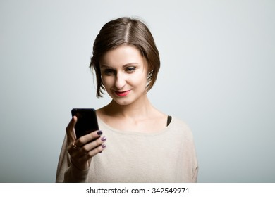 Pretty girl looks at mobile phone, shocked, bright lifestyle photo, isolated on a gray background