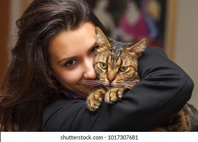 Pretty girl loving her pet tabby cat.