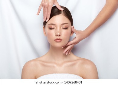 pretty girl lying down and receiving facial treatment, woman with naked shouders having massage for her face, body theraphy