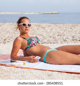 Pretty girl lying on the beach and sunbathing with phone in her hand