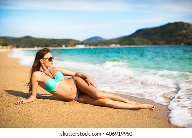 Pretty girl lying on a beach in a bikini and enjoying on sand by the open sea.