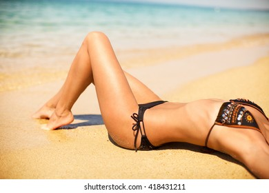 Pretty girl lying on a beach in a bikini