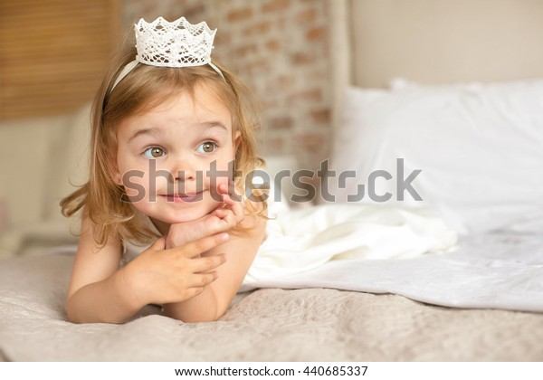 Pretty girl lying on the bed, and posing for a photograph Pretty emotional girl