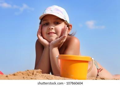 Pretty girl lying on sand beach in sunny day