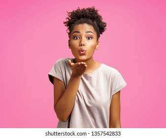 Pretty girl makes air kiss into camera, expresses her love. Photo of african american girl wears casual outfit on pink background. Emotions and pleasant feelings concept.