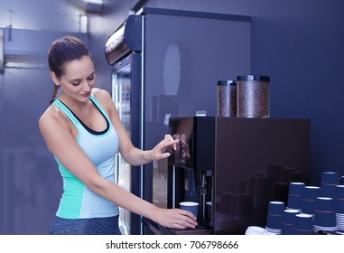 Pretty girl making coffee in disposable cup from coffee machine