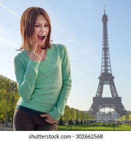 Pretty girl making funny faces in Paris, France on Eiffel Tower background