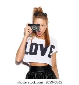 Pretty girl making photo using noname retro camera. White background, not isolated
