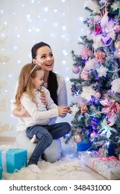 The pretty girl with mum sitting near Christmas tree in the house. Happy family. Merry Christmas and New Year.