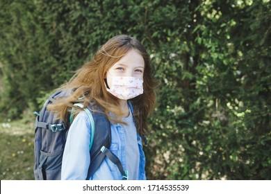 hübsches Mädchen mit Nasen-Mund-Maske geht nach der Korona-Quarantäne zur Schule