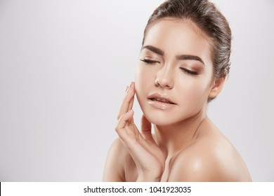 Pretty girl with nude make up and naked shoulders posing at grey background, beauty photo concept, skin care, hydrated skin,closed eyes.