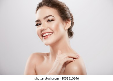 Pretty girl with nude make up and naked shoulders posing at grey background, beauty photo concept, skin care, hydrated skin.
