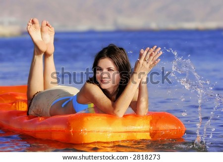 pretty girl on air mattress floating on sea