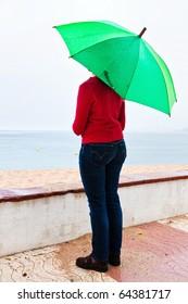 Pretty girl on the beach on a rainy afternoon