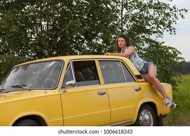 Pretty girl on top of retro car