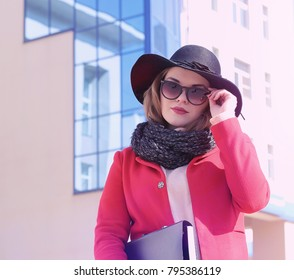 Pretty girl on a walk in red coat in city