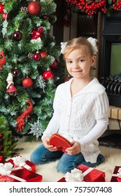 Pretty girl open a red gift box near christmas tree and fireplace